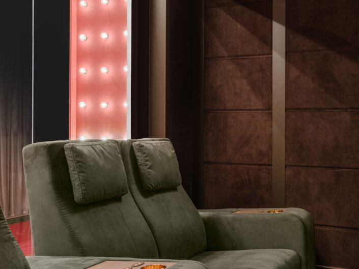 Cinema room in house with green comfortable chairs